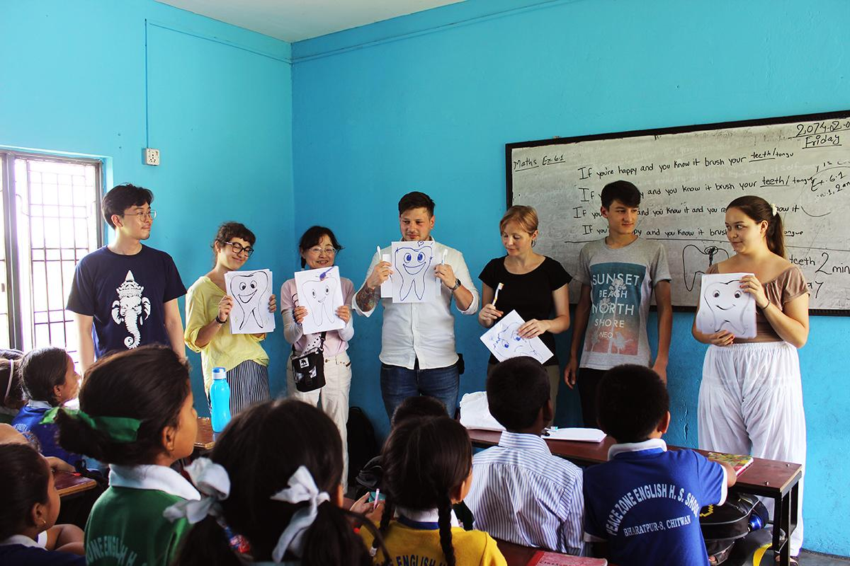 A group doing medical internships in Nepal help teach young children about oral hygiene at a local school.